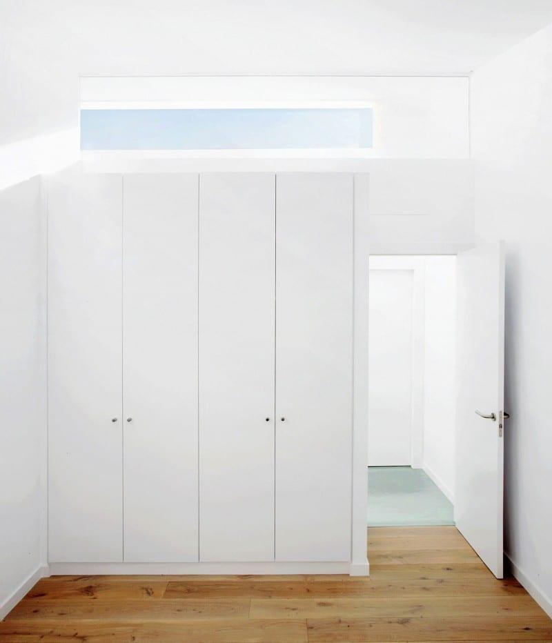 eingebauter weißer Kleiderschrank und natürliche Zimmerbeleuchtung dürch oberlicht an der wand