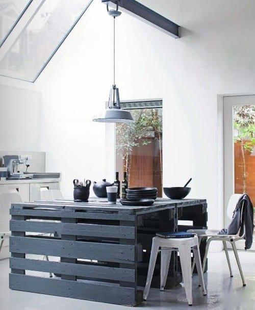 schwarzer esstisch aus paletten in weißer küche mit geneigtem Dach und oberlichtern