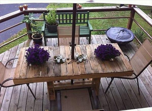 Esstisch aus paletten mit blumen-tischdekoration für die terrasse