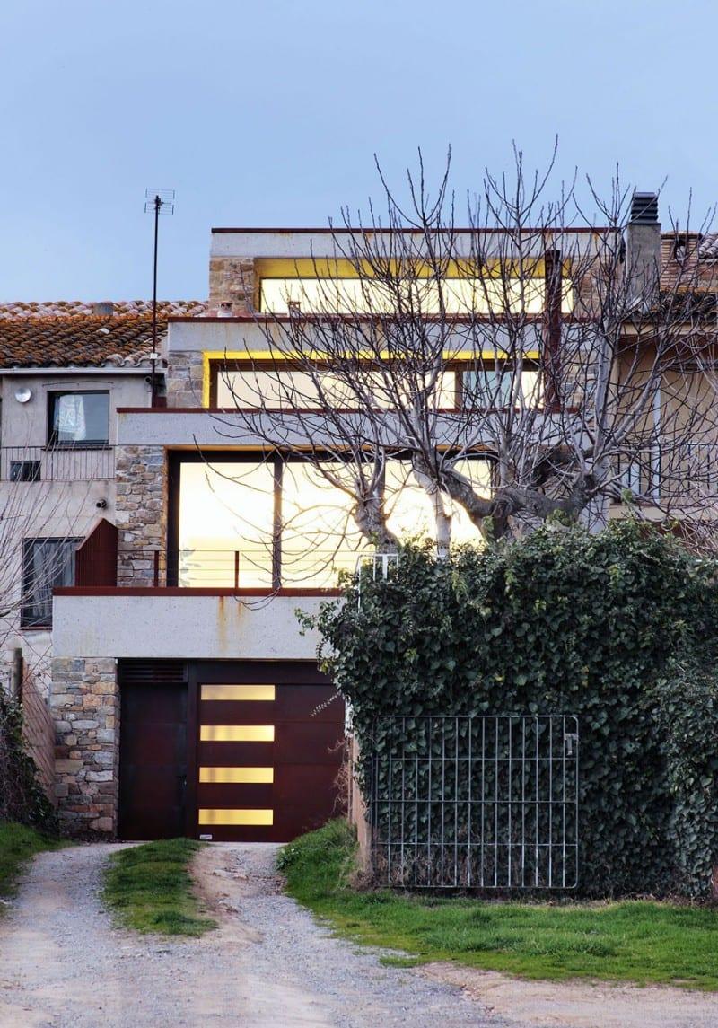 terrassiertes haus mit flachdach und mauerwerk aus natursten mit großformatigen fenstern