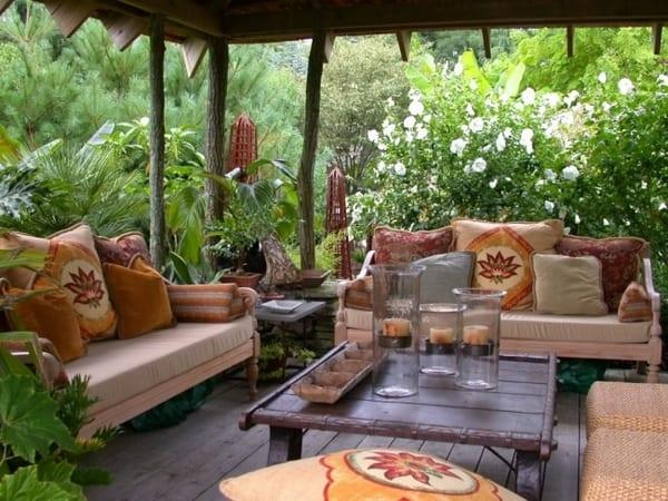 terrassengestaltung mit Sofa und Rattanhockern