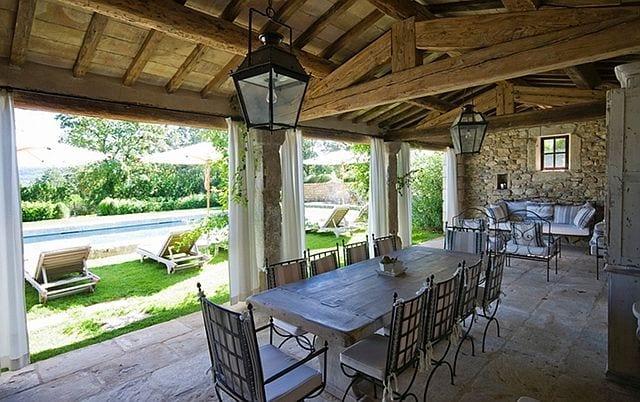 Terrasse mit Natursteinboden mit Holzesstisch und Metallstühlen-Natursteinstützen-weiße Gardinen für aussen- schwarze laternen