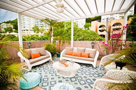 frische Terrassegestaltung mit weißen Terrassenmöbeln und blauem Teppich