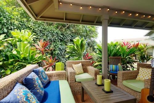 Gartenmöbel mit grünen Sitzkissen und blaue Dekokissen