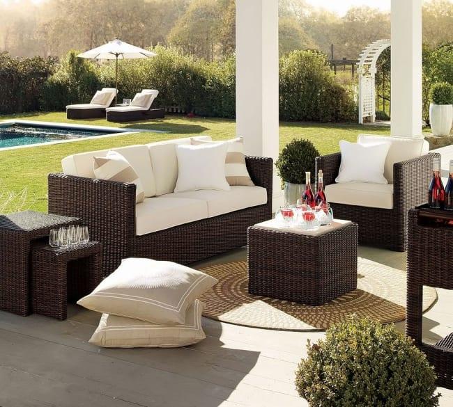 Überdachte Terrasse mit Holzboden und Rundteppich- Rattanmöbel mit weißen Polsterkissen- Kissen in weiß und beige