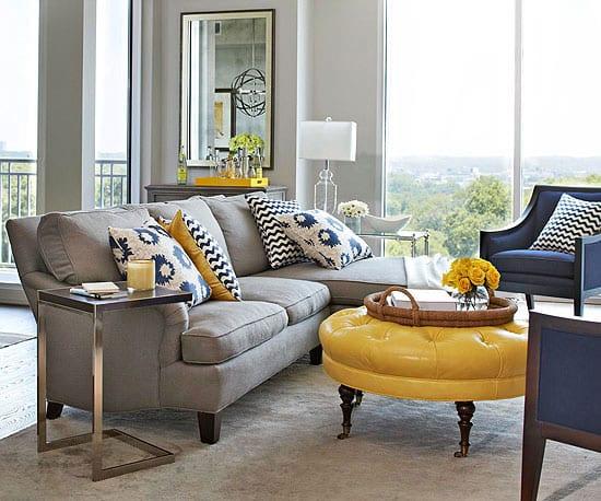 Teppich grau- sofa grau- lederhocker gelb- blaue sessel- dekokissen in weiß und blau