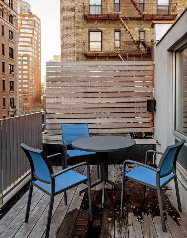 kleine loft terrasse mit holzboden und blauen stühlen
