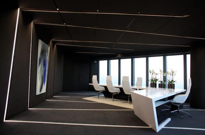 moderne Inneneinrichtung mit schwarzen wänden und schwarzer Decke- L förmiger Schreibtisch in weiß- Teppich grau mit weißen linien