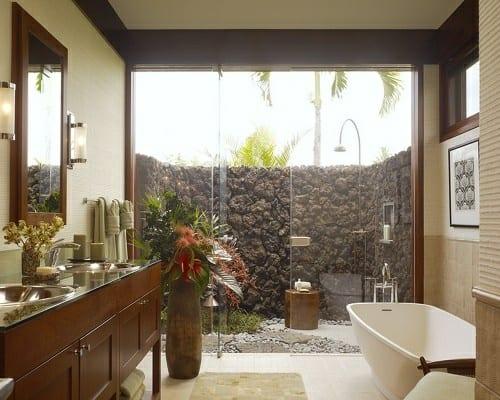 badezimmer einrichten mit offenem Steingarten und outdoor dusche- bademöbel aus holz und weiße freistehende badewanne