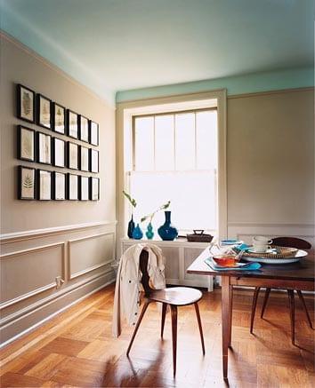 hellblaue decke und taupe Wandfarbe- interir mit parkettboden und wandgestaltung mit schwarzen bildrahmen