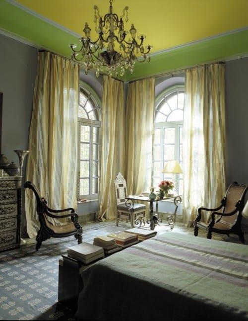 schlafzimmer gestaltung mit gelber decke und kroneleuchte- gardinen weiß und gelb-rustikale holzstühlen-bogenfenster