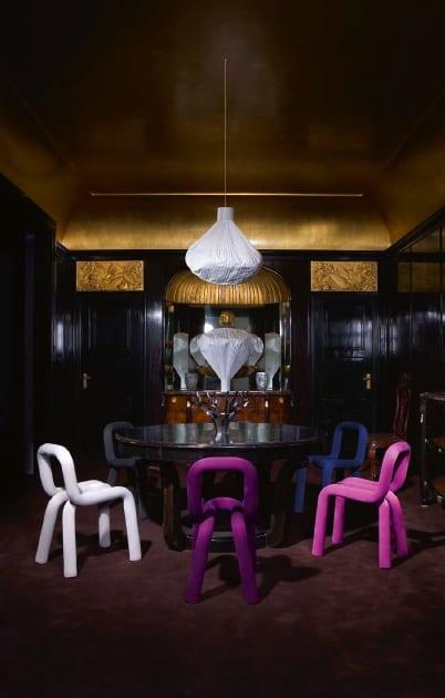 modernes wohnzimmer einrichten mit schwarzen wänden und goldener decke-schwarzer Rundtisch mit kreative Farbstühlen