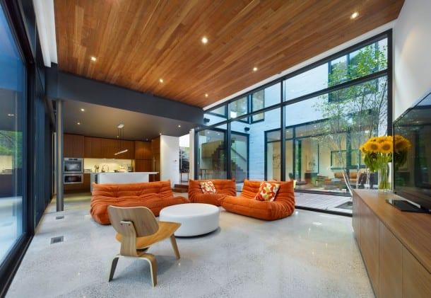 minimalistisches wohnzimmer einrichten mit holzdecke und glasfassade- natursteinboden-orange seats and sofas- weißer rundhocker