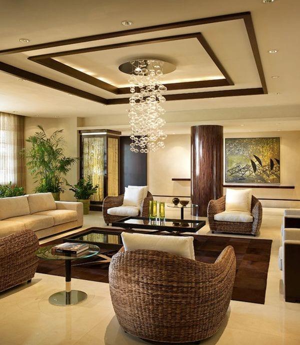wohnzimmer einrichten-rattanmöbel mit weißen sitzkissen-runde stütze aus naturstein- weißer marmorboden mit braunem teppich- moderne deckenleuchte