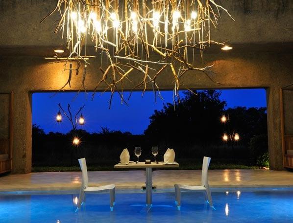 indoor pool- kreative deckenleuchte- weiße stühle mit weißem tisch