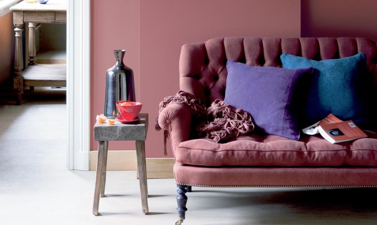 wand und sofa in Taupe Farbe- kissen in violett und blau
