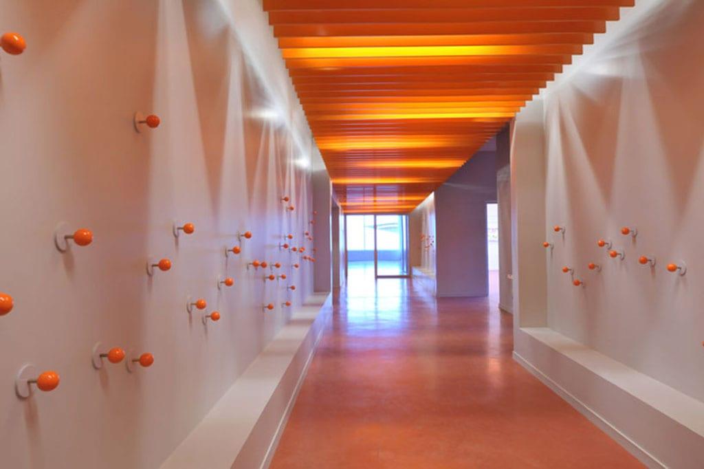 Flur gestaltung mit orangen Kleiderhängern und orangen Schallpanelen