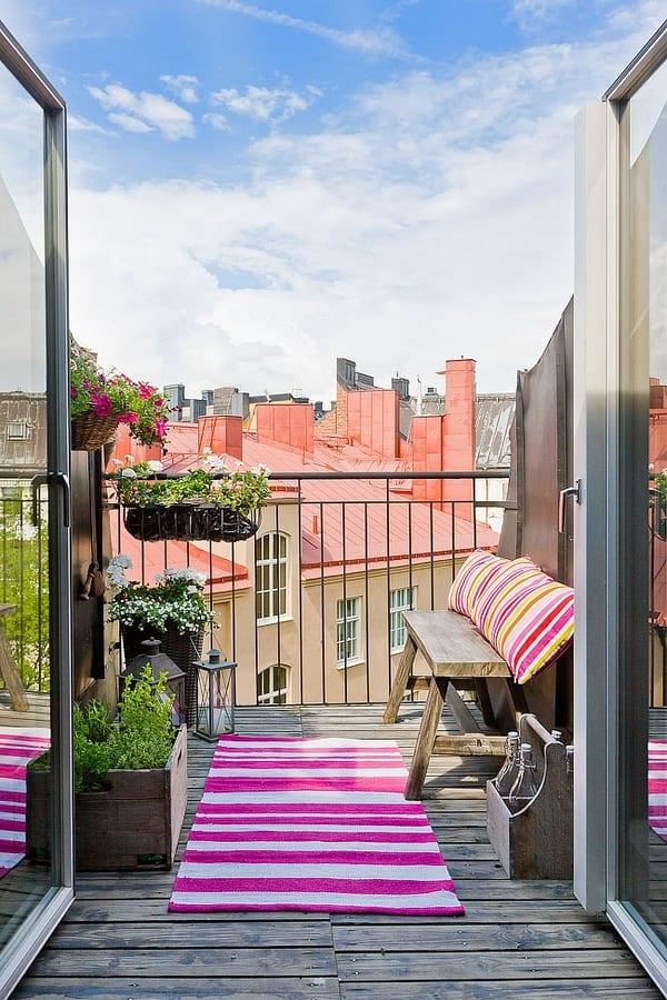 terrassengestaltung mit farbigen Teppich und Kissen- Terrasse mit Holzboden und kleiner Holzbank