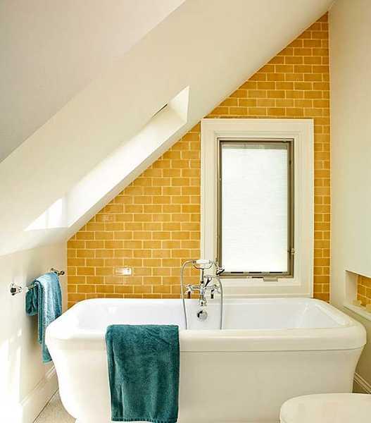 gelber ziegelmauerwerk - weiße freistehende badewanne- Dachfenster- blaue Badetücher
