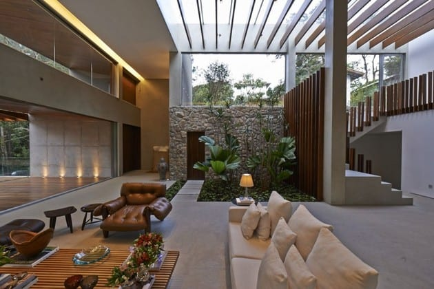 innenraumgestaltung mit betonboden und oberlicht mit holzlamelen-wandgestaltung mit naturstein und holz-wohnzimmer gestalten mit weißem sofa und Holzteppich-panoramafenster zur holzterrasse