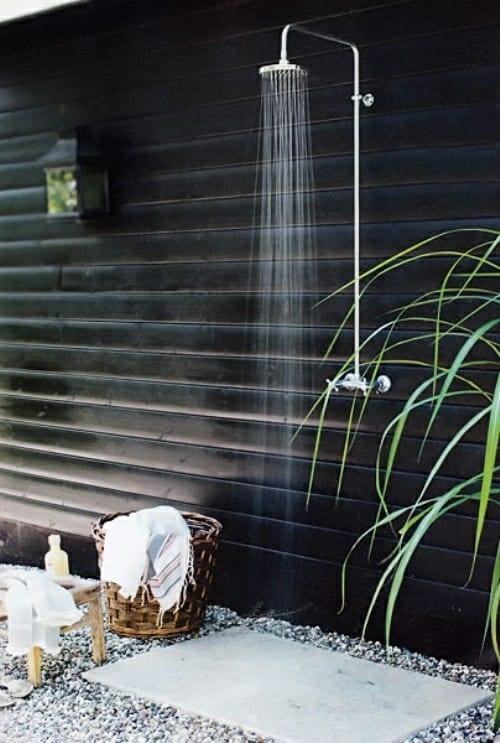schwarze Wand aus Holzverkleidung mit außendusche