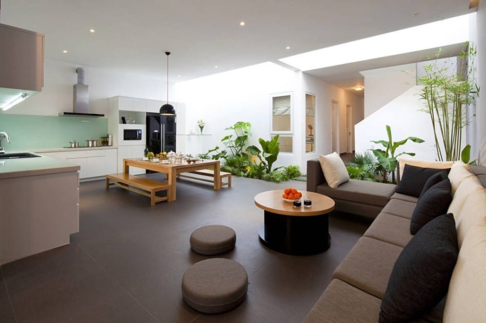 modernes interior design mit weißer küche und garten im Wohnzimmer-ecksofa mit schwarzen kissen und rundtisch-natursteinboden-holzesstisch mit holzbänken-offene küche einrichten