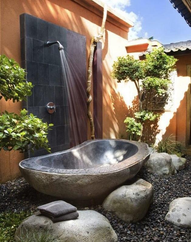 outdoor dusche mit schwarze Natursteinwand und freistehende badewanne aus naturstein