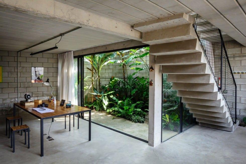 raumgestaltung mit betonboden und betondecke-wohnzimmer mit betontreppe und yutongwand-schiebetüren mit schwarzen rahmen-holztisch mit schwarzen metallfüßen