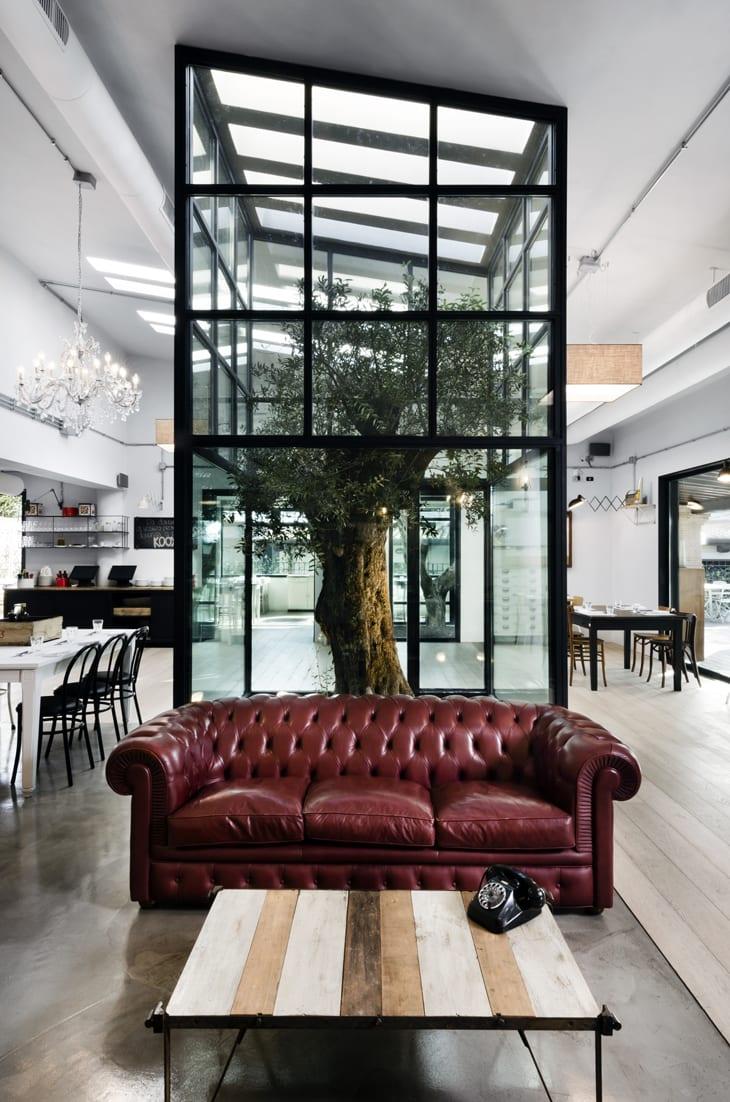 Raumgestaltung mit weißen wänden und schwarzen Fensterrahmen- Holzesstisch weiß und schwarz-kronenleuchte-couchtisch mit holzbrettern