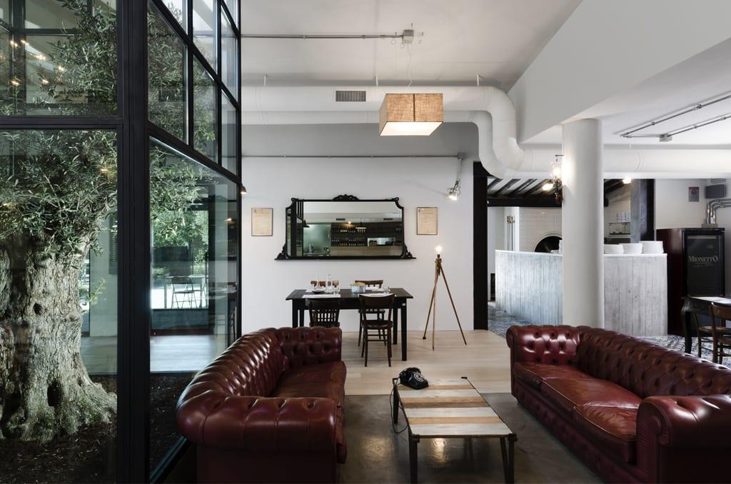 rote ledersofa bordeaux-weiße runde Stützen-Wandspiegel mit schwarzem Rahmen- rechteckige Penldelleuchte- weiße Wände