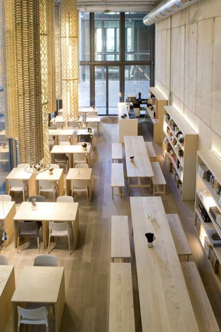interior design mit Boden aus Eichenholz und Sichtbetonwänden- moderne Pendelleuchten mit handgewebten Weidenkörben- Holzesstische