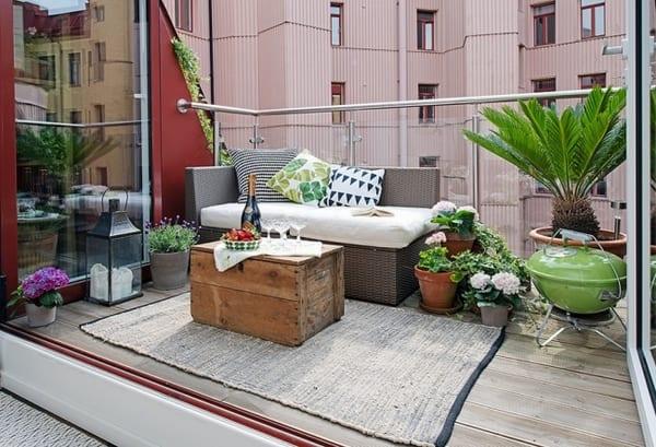 terrassengestaltung mit kleinem Sofa aus Rattan und Holzklotz für Couchtisch- Terrasse mit Teppich und Holzboden