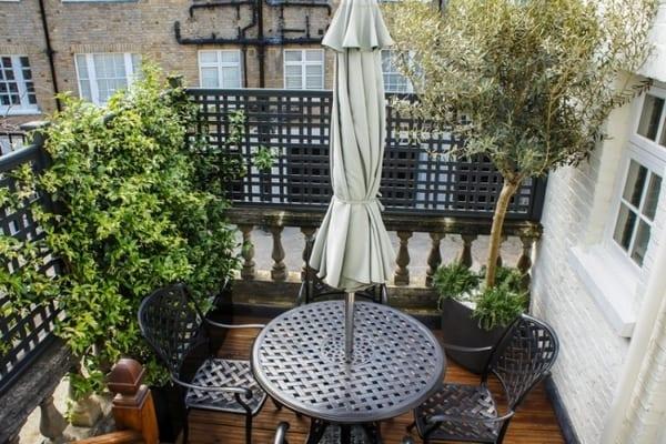Umbau kleiner Terrasse mit Holzboden und schwarzem Geländer aus Metallgitter