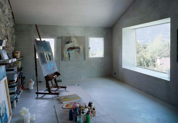 Atelier aus beton bauelemente mit natursteinwand und bücherregalen- große und kleine fensteröffnungen