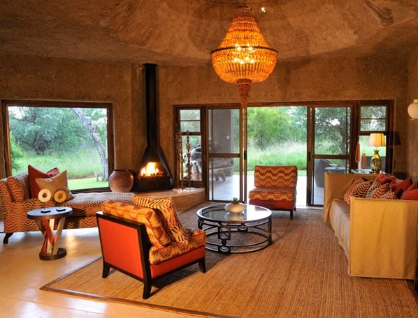 Luxus Wohnzimmer Gestaltung mit Liege und roten Sesseln- offene kamin-runde couchtische