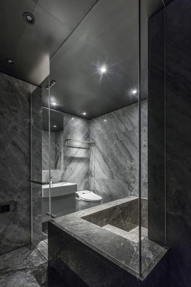 kleines Badezimmer aus Marmor mit Glaswand- Dusche mit natursteinbadewanne
