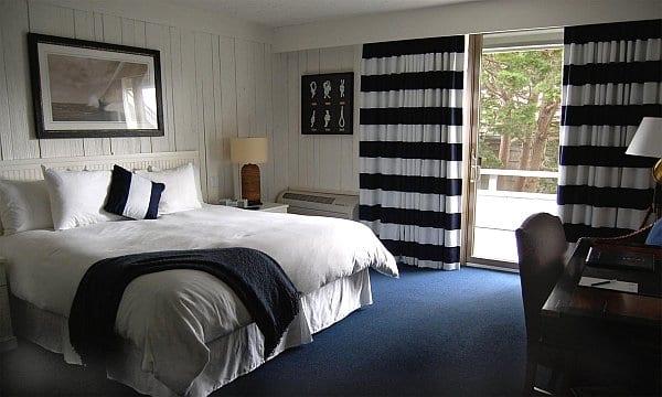 Schlafzimmer mit weißen Wänden und maritimen Gardinen- weiße bettwäsche und blaue bettdecke
