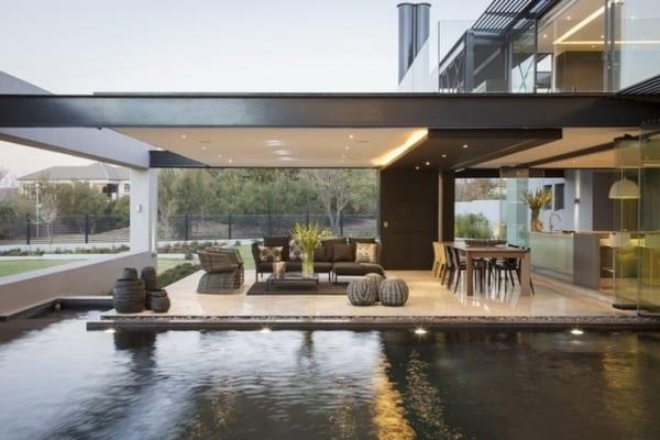 modernes haus mit pool und überdachter terrasse - minimalistische Terrassegestaltung in weiß und schwarz