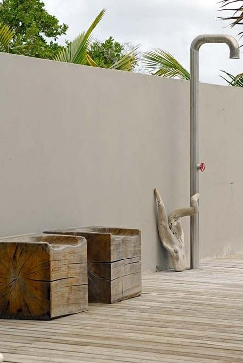 weiße Gartenmauer und holzbodenbelag im garten- hocker aus holzklötzen