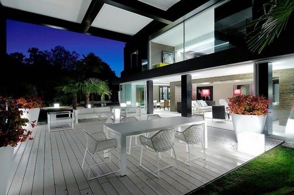 überdachte Terrasse mit weißem Holzboden und weißen Terrassenmöbeln- weiße Überdachung mit sichtbarem Tragkonstruktion aus schwarzen Metallträgern