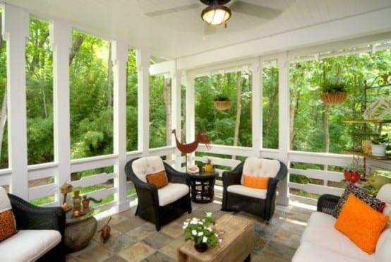 weiße Holzüberdachung- schwarze Gartenmöbel aus Rattan- orange kissen