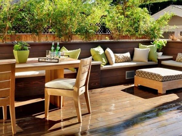 holzterrasse mit Sitzbänken aus holz mit weißen Sitzkissen und grünen Kissen