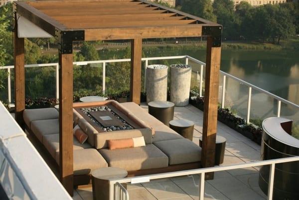 Terrasse mit rechteckiger Holzlaube und Außenkamin in der Mitte- Glasgeländer