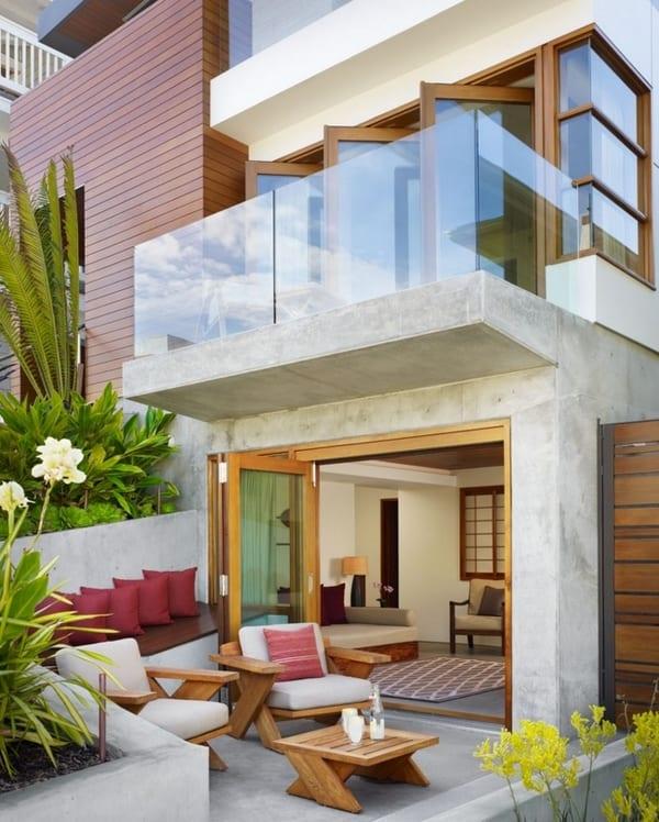Moderne Terrasse mit Holzgartenmöbeln- modernes Haus mit Betonterrasse und Glasgeländer und drehbaren Fenstertüren
