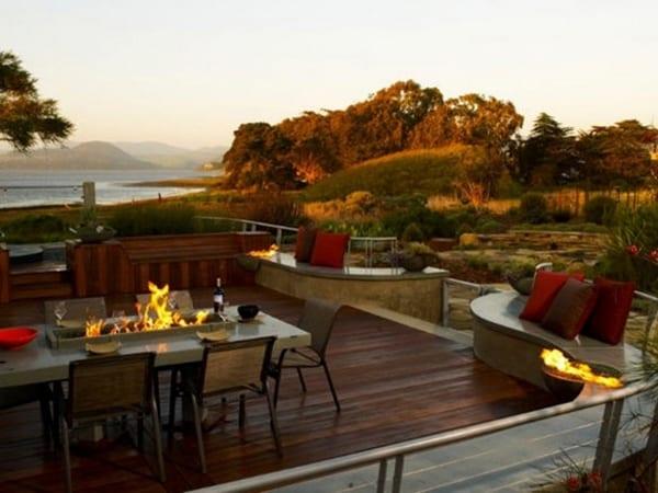 Terrasse mit Holzboden und Umrandung aus Naturstein als Sitzfläche
