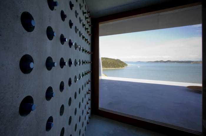 Betonwand mit Lochung für Weinflaschen- Weinkeller Panoramafenster und Terrasse