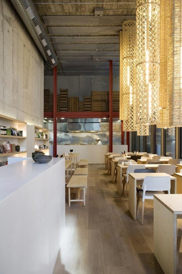 interior mit Holzboden und Sichtbetonwänden- weiße Theke und Metallständerkonstruktion