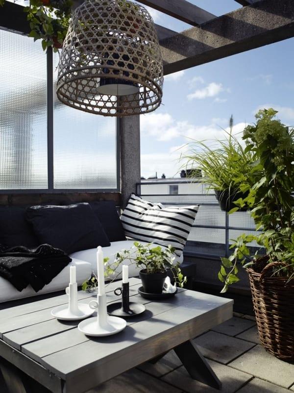 überdachte terrasse mit Pflasterplatten und grauen Holzmöbeln- pendelleuchte mit  Weidenkorb