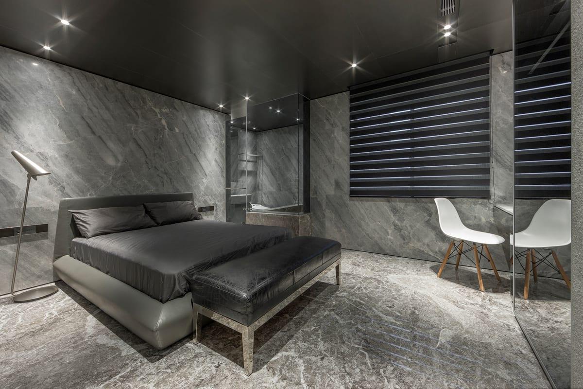 graues bett mit bettwäsche grau- marmorwände- moderne stehleuchte- graue fensterrolladen