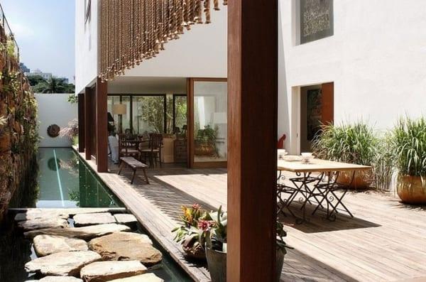 terrasse mit holzboden und begrünter Natursteinwand- Holzstutzen und Außenwandgestaltung mit hängenden Seilen